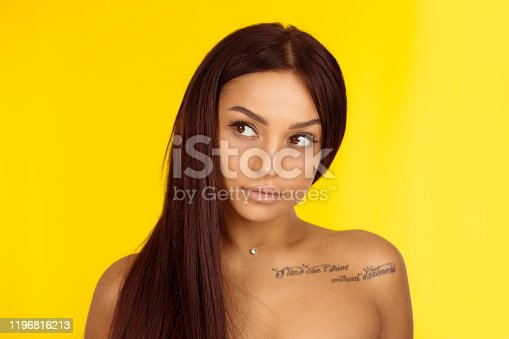 Beauty woman portrait with black hair and tattoo on chest stars cannot shine without darkness. Beautiful girl looks to side. Multiracial Caucasian African American female isolated on yellow background