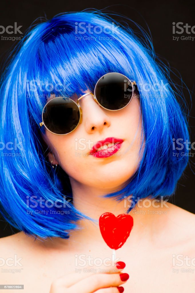 Beauty Woman With Blue Wig And Sunglasses and holding with her hand a candy with heart shape royalty-free stock photo