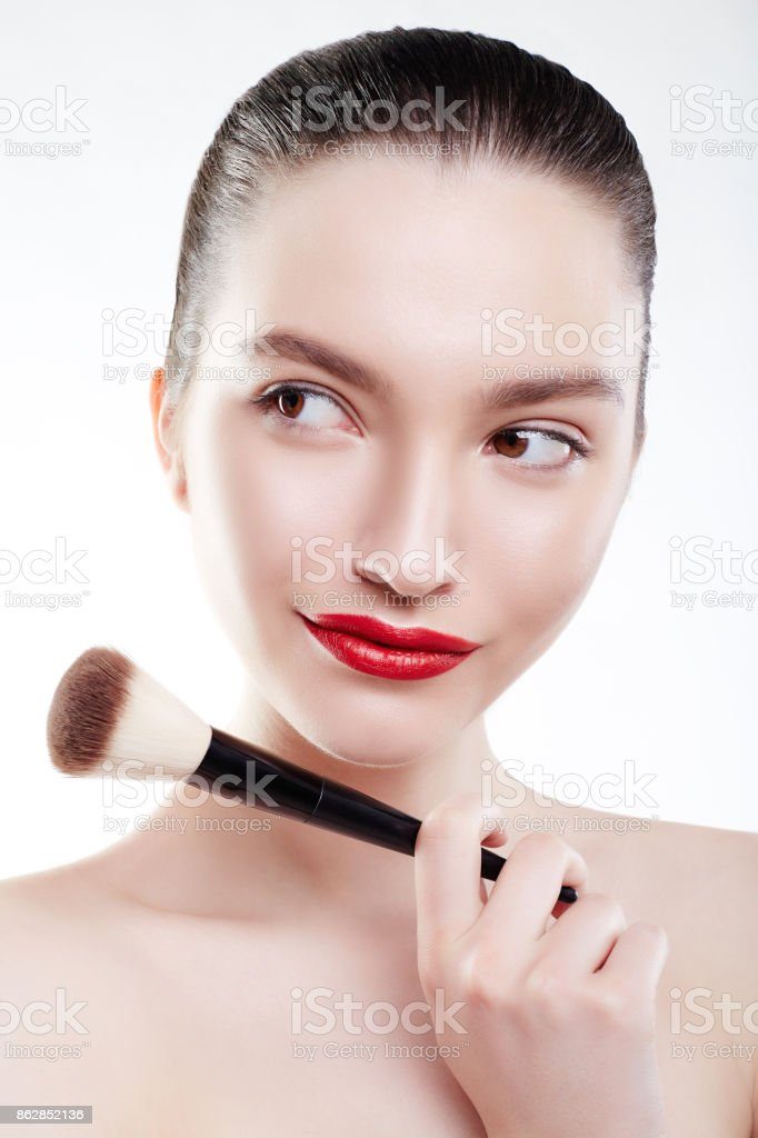 Beauty Woman with Makeup Brush isolated on white background. Make-up for Brunette Model Girl with Brown Eyes. Beautiful Face. Perfect Skin with Red Lips and white teeth. stock photo