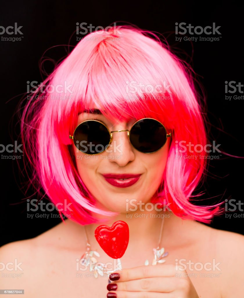 Beauty Woman With Pink Wig And Sunglasses and holding with her hand a candy with heart shape photo libre de droits