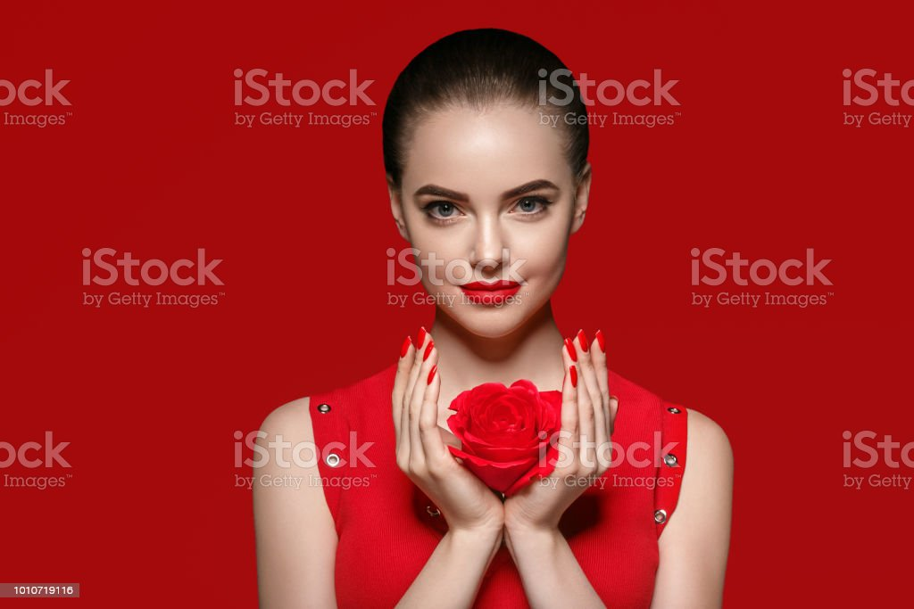 Beauty woman with rose flower beautiful curly hair and lips. Studio...