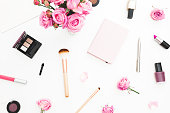 Beauty workspace with pink roses bouquet, cosmetics, diary on white background. Top view. Flat lay home feminine desk. Fashion blog
