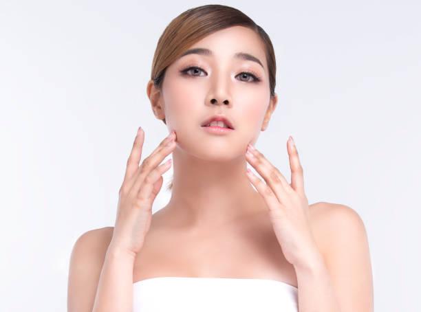 Beauty Junge asiatische Frau mit perfekter Gesichtshaut. Gesten für die Werbebehandlung Spa und Kosmetologie. – Foto