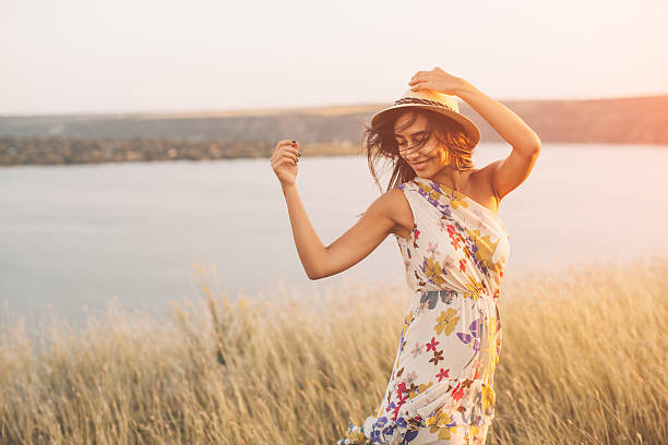 Beauty young girl outdoors enjoying nature Beauty young girl outdoors enjoying nature. Fashion young woman in floral dress and stylish hat in meadow with copy space dress stock pictures, royalty-free photos & images