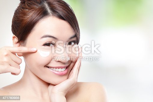 istock Beauty young woman applying cosmetic cream 471783935