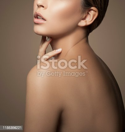 Lips, hand, shoulder of beautiful girl. Natural lips, nude make-up, beige background