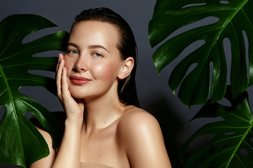 Beauty. Young woman portrait with fresh green exotic tropical leafs.
