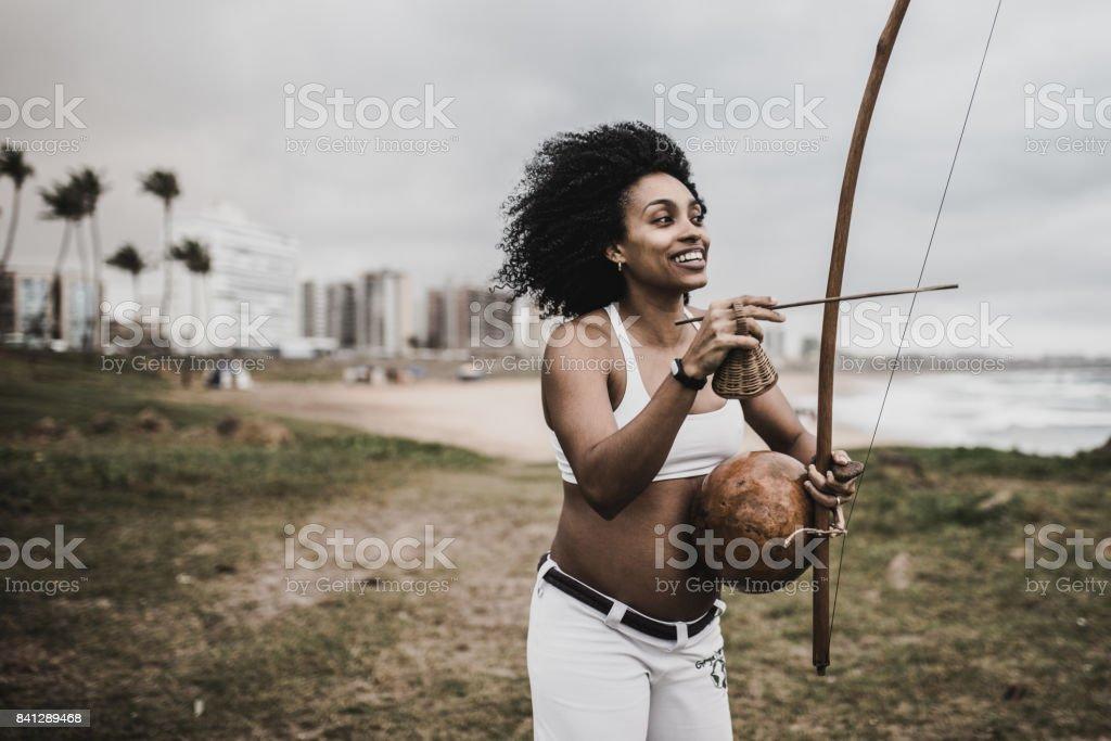 afro-brasileiro linda mulher tocando berimbau na praia - foto de acervo