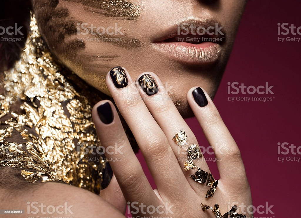 Beautyful girl with gold glitter on her face and design