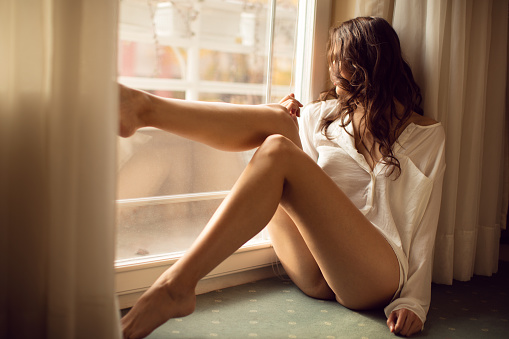 Beautyful young blond woman sitting next to the balkony door