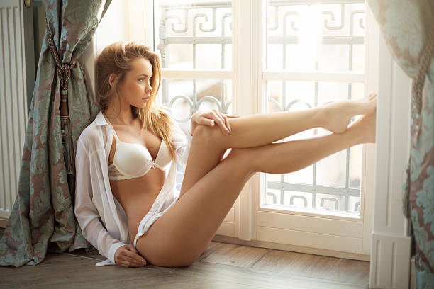 beautyful young blond woman sitting next to the window - body part stock pictures, royalty-free photos & images