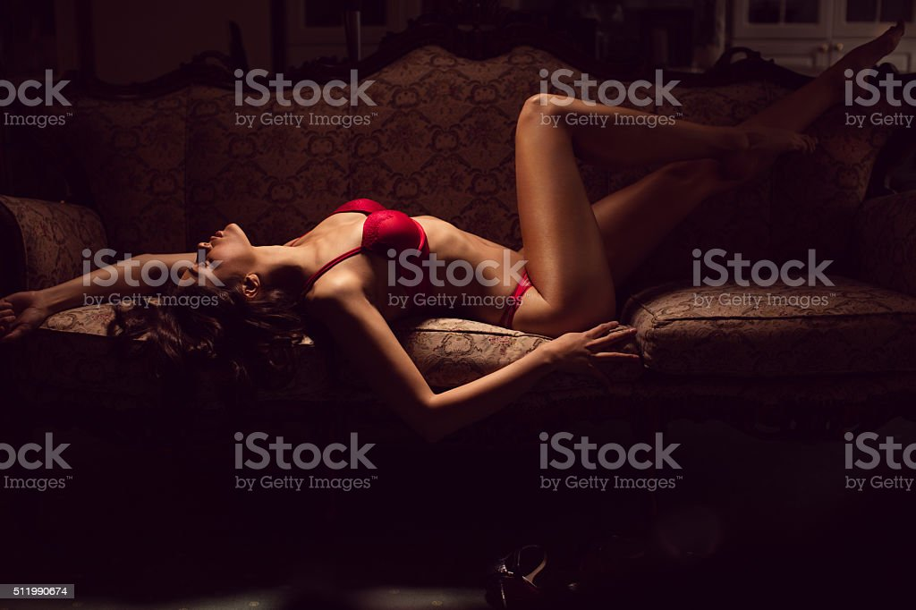 Beautyful young woman in lingerie lying on the sofa stock photo