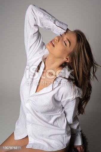 506435758 istock photo Beautyful young woman in man's shirt 1207975311