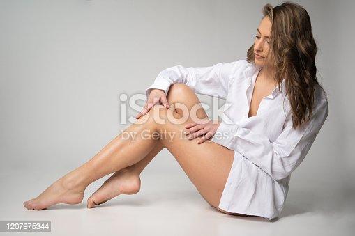 506435758 istock photo Beautyful young woman in man's shirt 1207975344