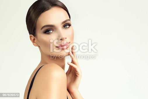 Beauty-style portrait of appealing, young woman. Smokey-eyes style bright makeup and hair gathered in a tuft, tender look on viewer. Makeup, cosmetology and beauty technologies.
