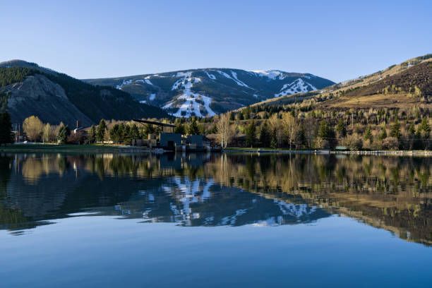 Beaver Creek Reflected in Nottingham Lake Avon Colorado Beaver Creek Reflected in Nottingham Lake Avon Colorado - Scenic view with ski runs and snow reflected in lower valley lake where it's spring. avon colorado stock pictures, royalty-free photos & images