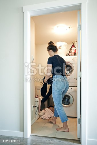Shot of a young woman doing laundry at home