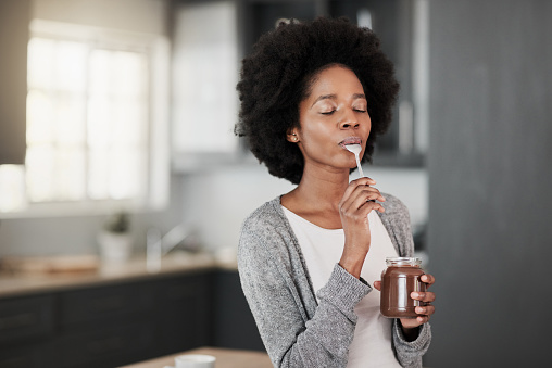 Shot of a young woman eating chocolate from a jar at home