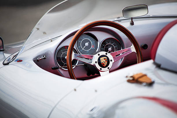 Beck Porsche 550 Spyder Halifax, Nova Scotia, Canada - June 16, 2012: At a public car gathering, a Porsche 550 Spyder replica interior. Focus on steering wheel with instrument panel and dash mounted rearview mirror visible inside the car. Asphaly surface visible in front of car and out of focus.  The 550 Spyder is one of the most replicated of classic automobiles with numerous companies creating almost exact replicas of the car. porsche stock pictures, royalty-free photos & images