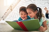 Shot of two adorable young siblings reading a book together at home