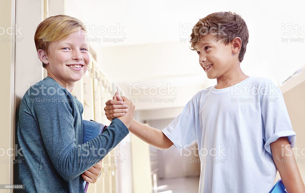 Becoming the best of friends! Cropped view of two young schoolboys making friends and shaking hands 10-11 Years Stock Photo