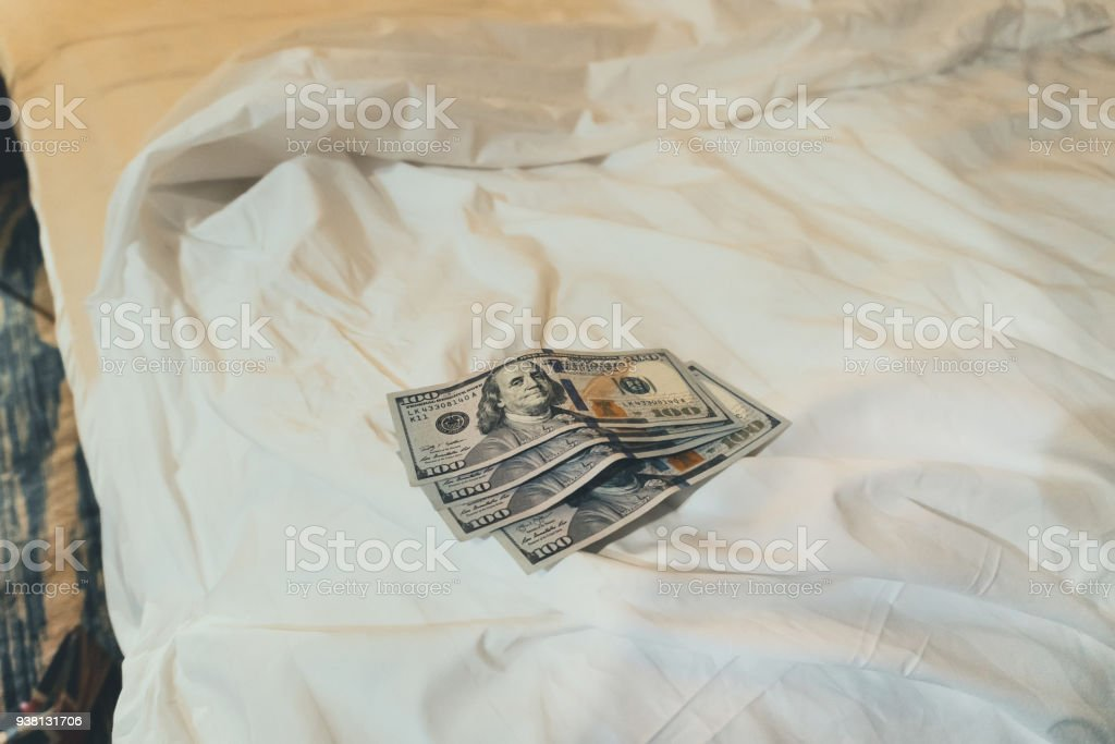 bed and money to symbolize the cost of sex. stock photo