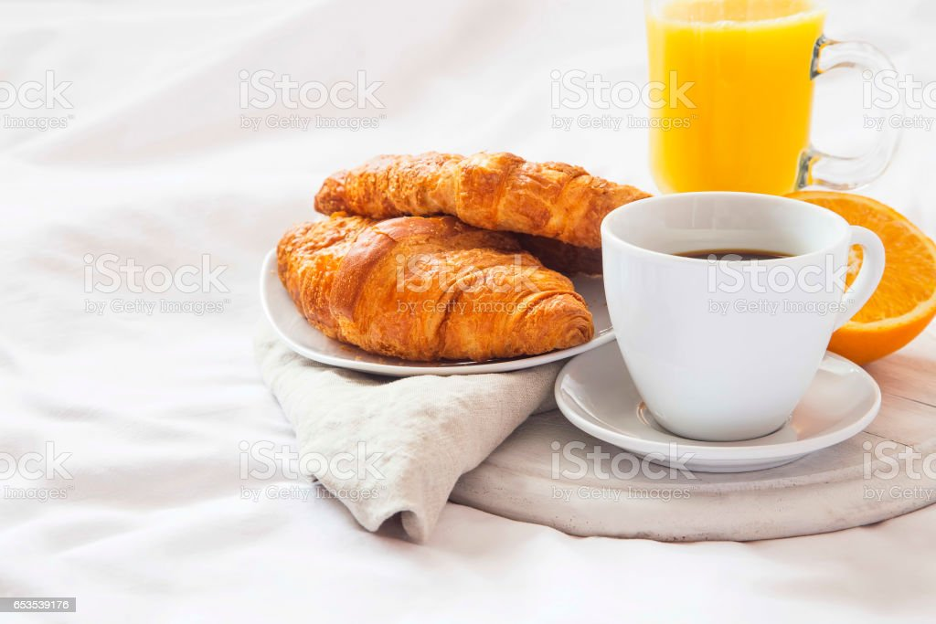 Bed breakfast with coffee cup, croissants and orange juice on white sheets stock photo