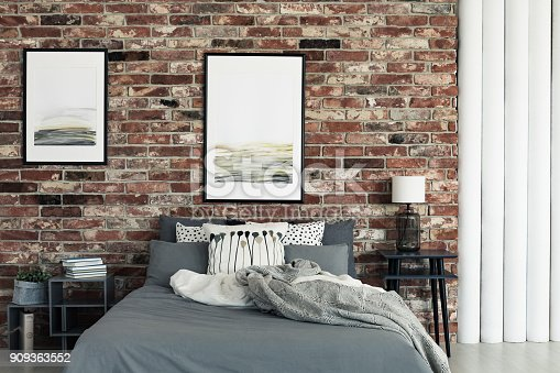 istock Bed by brick wall 909363552