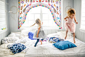 Two girls, sisters, friends, dance, play and jump on the bed in pretty outfits