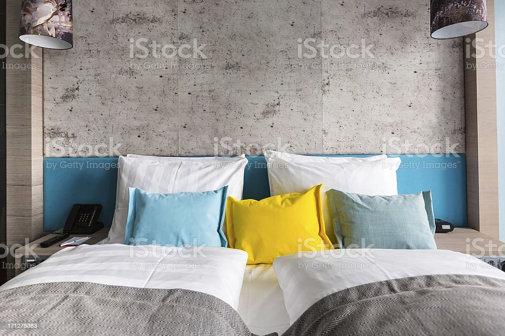 Bed in hotel room with colorful pillows stock photo