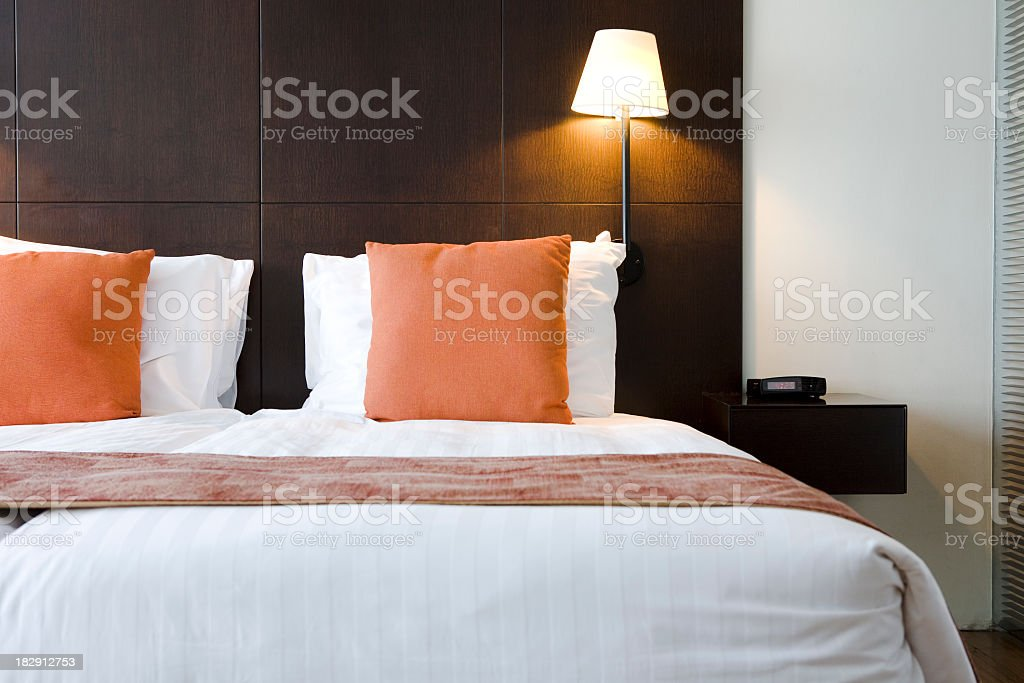 Bed in hotel room with orange pillows  stock photo