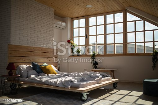 Comfortable, messy,  wooden bed in bedroom with bed sheet, in the morning