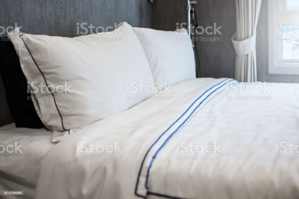 Bed maid-up with clean white pattern pillows and bed sheets in beauty...