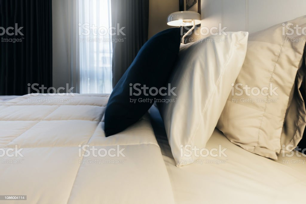 Bed maid-up with clean white pillows and bed sheets in beauty...