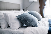 istock Bed maid-up with clean white pillows and bed sheets in beauty room. Close-up. Lens flair in sunlight. 1004263078