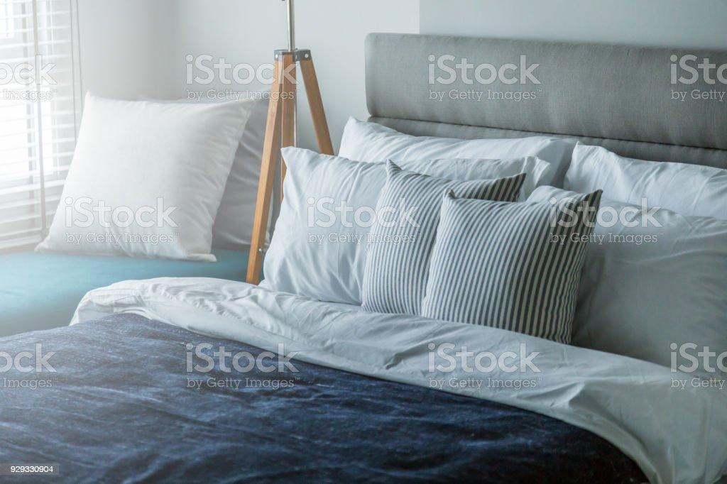 Bed maid-up with clean white pillows and bed sheets in beauty room....
