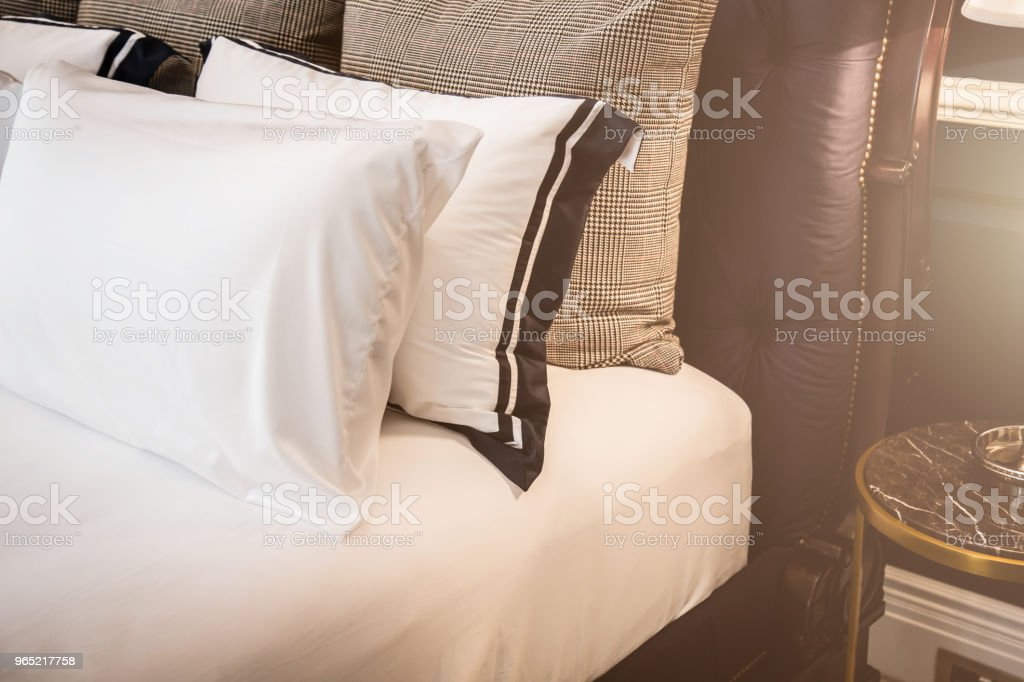 Bed maid-up with clean white pillows and bed sheets in beauty room. Close-up. Lens flair in sunlight. royalty-free stock photo