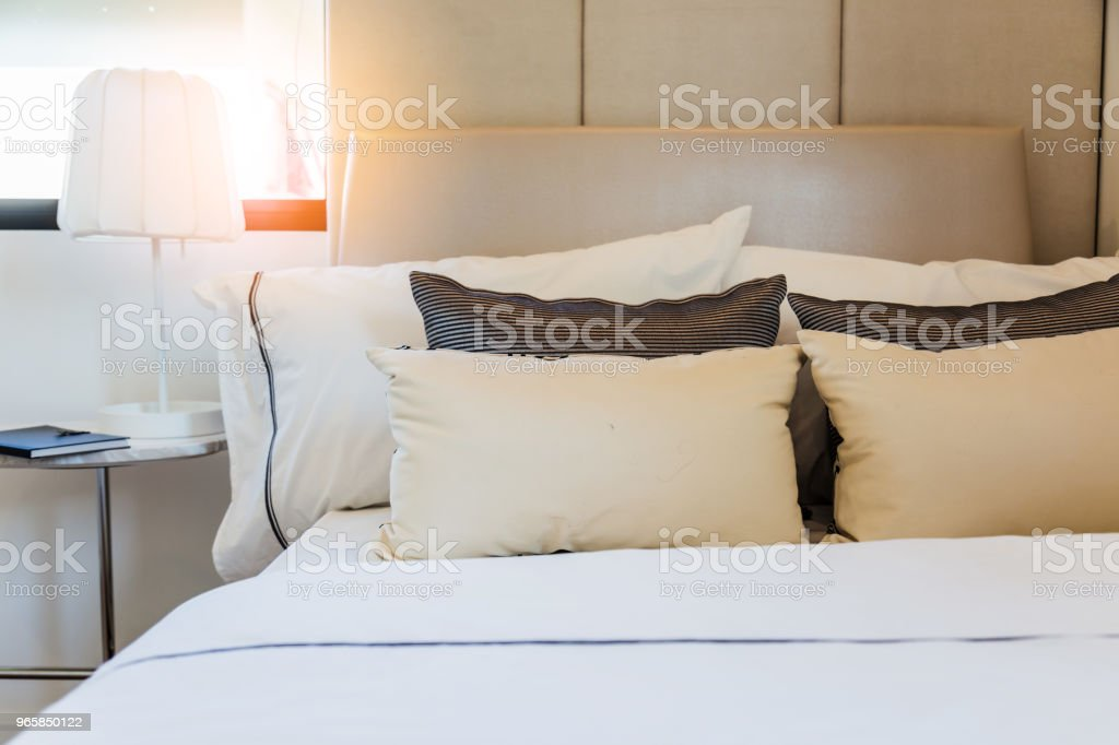 Bed maid-up with clean white pillows and bed sheets in beauty room. Close-up. Lens flair in sunlight. - Royalty-free Apartment Stock Photo