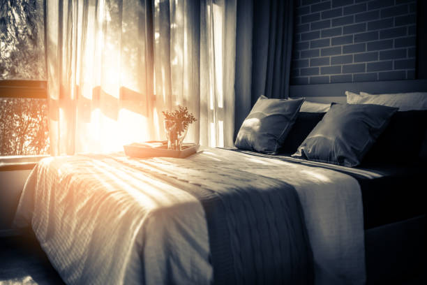 Bed maid-up with clean white pillows and bed sheets in beauty room. Close-up. Lens flair in sunlight. Bed maid-up with clean white pillows and bed sheets in beauty room. Close-up. Lens flair in sunlight. inn stock pictures, royalty-free photos & images