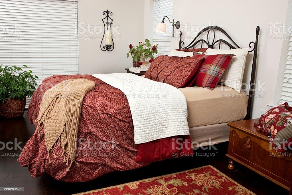 Bed room with dark wooden floor, throw rug, hope chest, queen size...