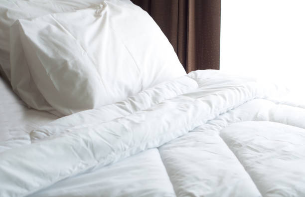 Bed sheet and pillow messed up in the morning stock photo