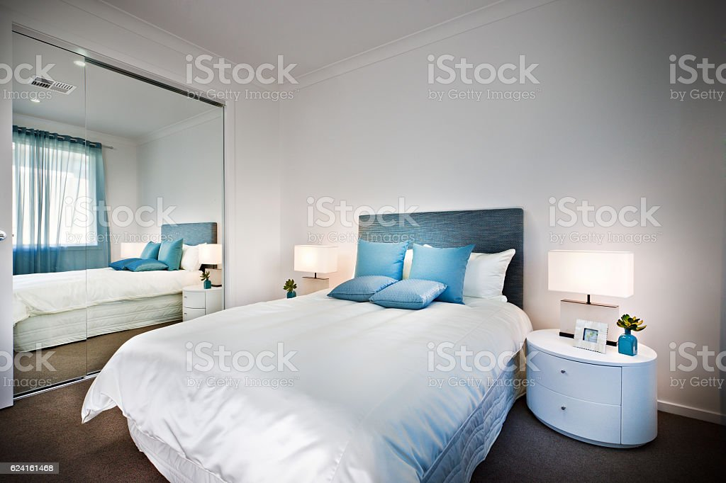 Bed with a huge mirror beside a lamp and table stock photo