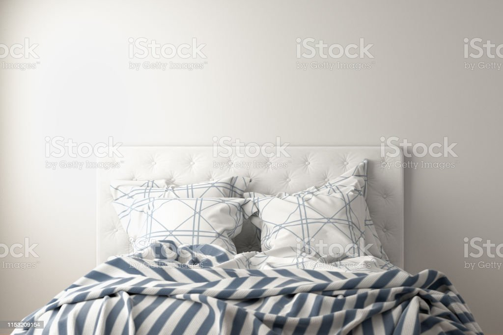 Top of unmade bed with duvet, bedding and pillows isolated on white....