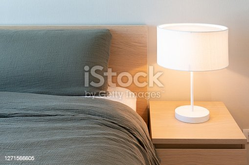 istock Bed with gray blanket and pillow with white electric lamp on the bedside table in bedroom interior. Minimalist comfort bedroom design for everyday living. Copy space, horizontal. Real image. 1271566605