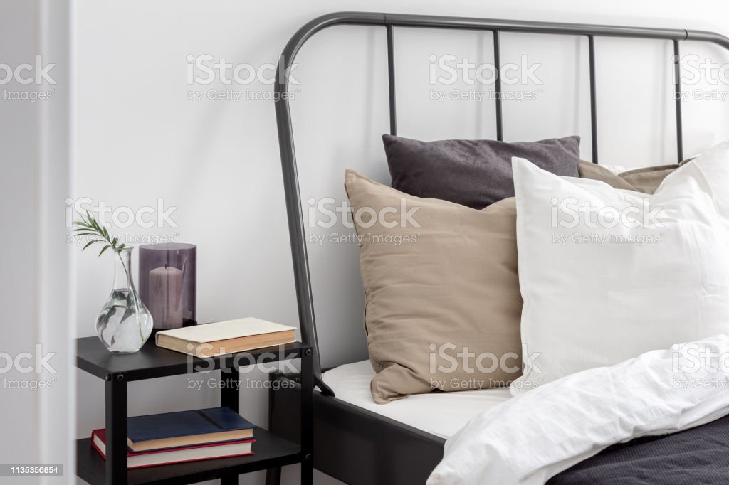 Simple bed with metal headboard and black wooden nightstand