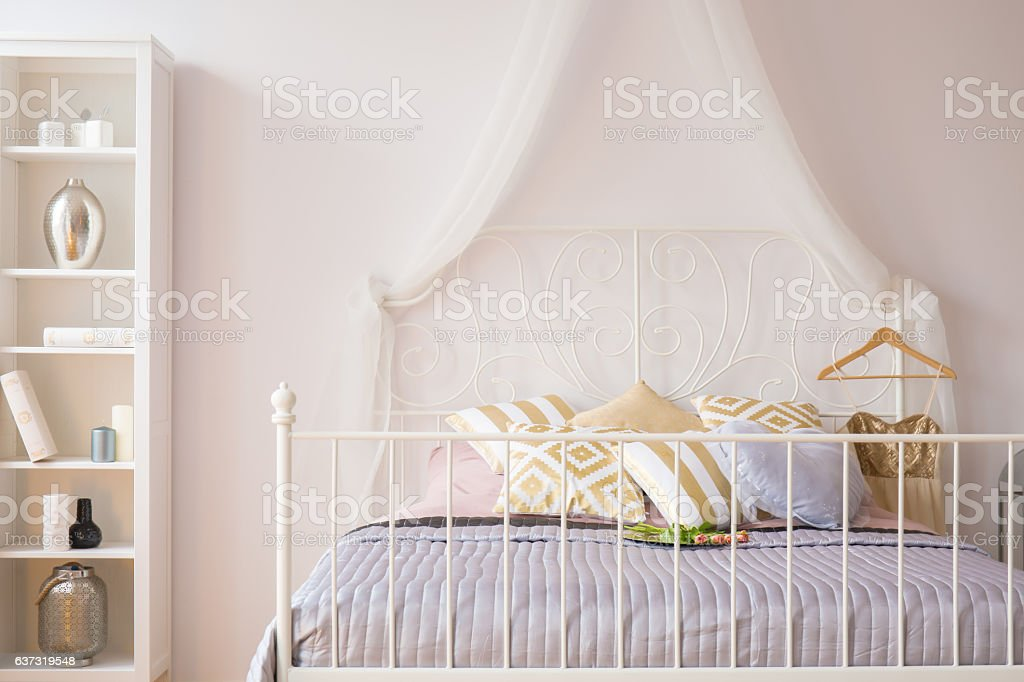 Room with bed with metal headboard and white bookcase