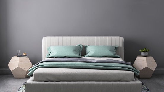 Interior bedroom close up with bed, pastel colored pillows, modern nightstand and wall lamp. Copy space template