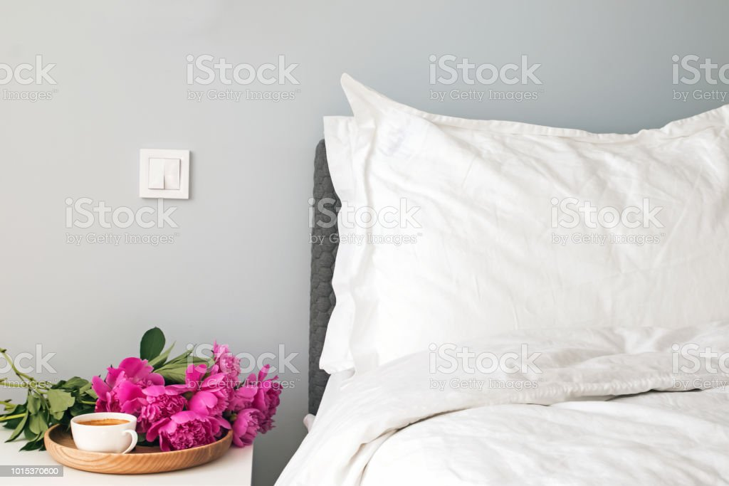 Bed With White Bed Sheets And Pink Peonies And Coffee On The Nightstand  Stock Photo - Download Image Now