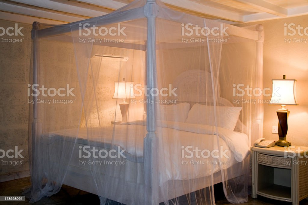 Bed with white canopy and illuminated lamps stock photo