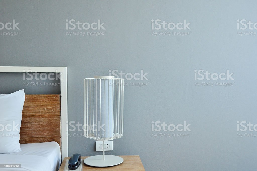 Bed with white linen beside night table with lamp stock photo